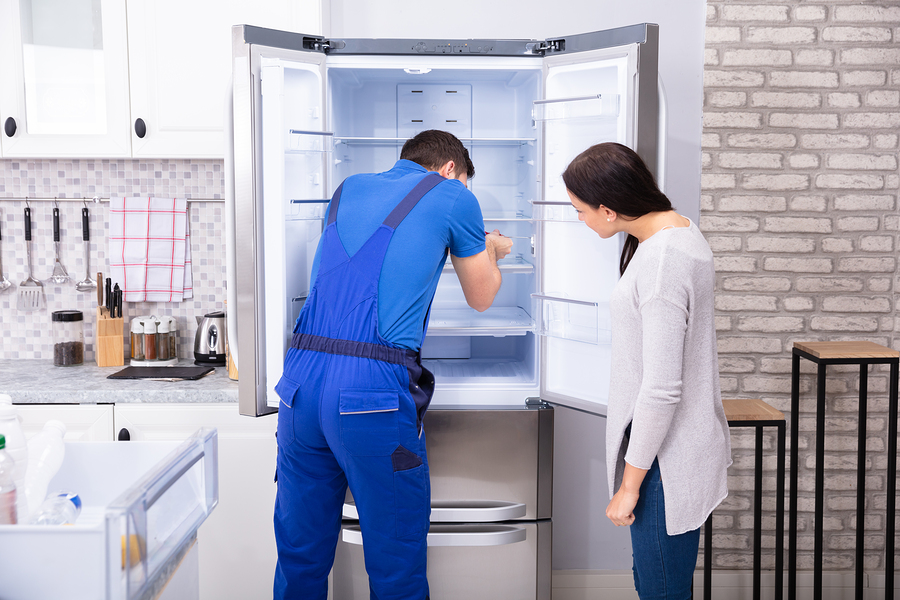 Woman Looking At Male Repairman Fixing Refrigerator With Screwdriver